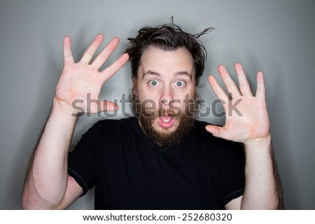 Man holding his arms up afraid from something - stock photo