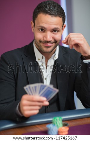Man holding his cards looking happy