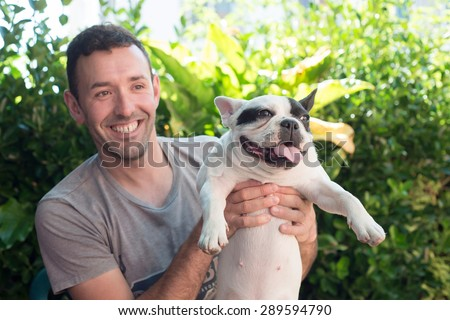 Man holding his dog, a beautiful French bulldog female - stock photo