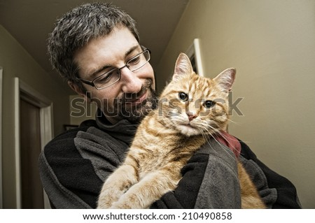 Man holding his ginger cat - stock photo