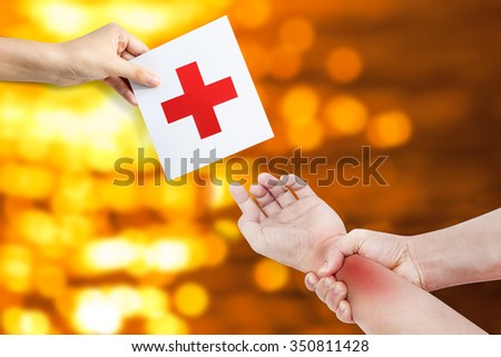 Man holding his hand pain concept with medicine cross sign, treatment unit