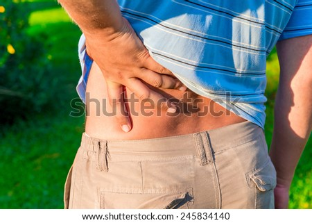 man holding his hand sore lower back - stock photo