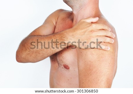 Man holding his shoulder because of a pain. - stock photo