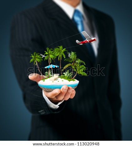 Man holding in  hand a tropical island - stock photo