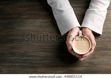 Man holding in hands cup of coffee on wooden background - stock photo