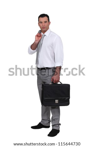 Man holding jacket over shoulder and holding briefcase - stock photo