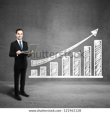 man holding laptop and profit on wall