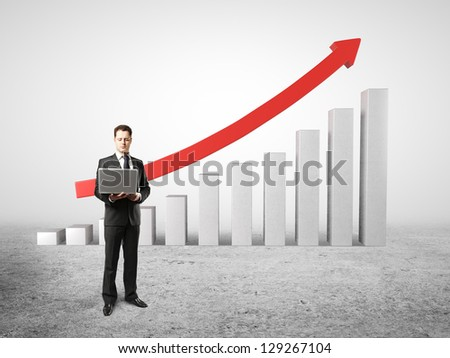 man holding laptop near of chart profits