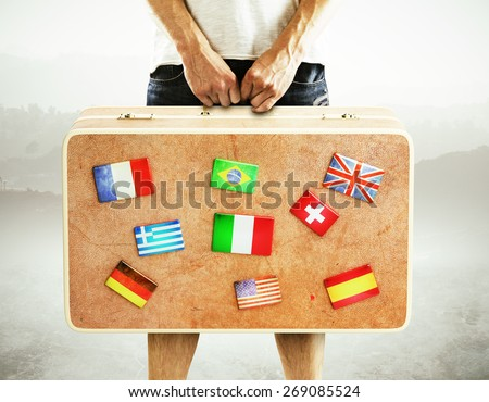 man holding leather  travel bag with flags - stock photo