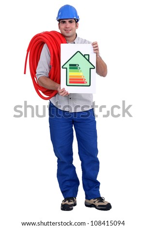 Man holding length of pipe and energy rating poster - stock photo