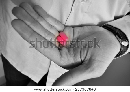 Man holding medicine in his hand - stock photo