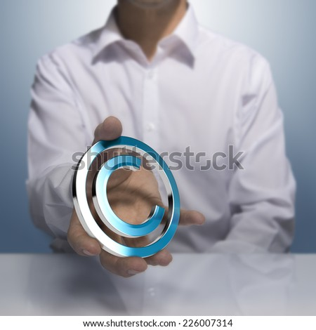 Man holding metallic copyright symbol. Concept image for illustration of author protection or intellectual property - stock photo