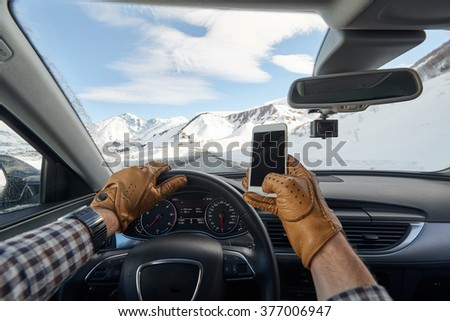 Man holding mobile phone inside luxury car interior with snowy mountains, dashboard and steering wheel in background