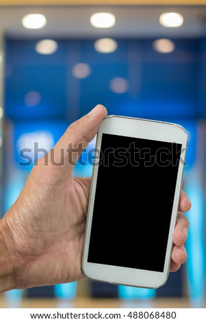 man holding mobile phone with blur ATM background
