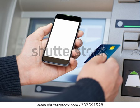 man holding mobile phone with isolated screen and a credit card at an ATM - stock photo