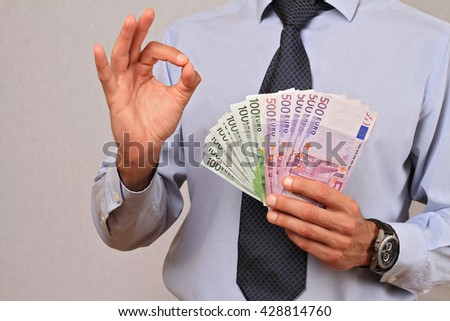 Man holding money and showing Ok sign.