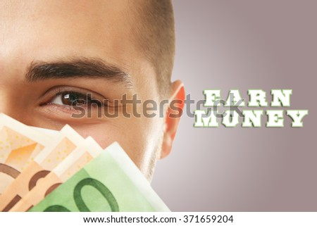 Man holding money on brown background - stock photo