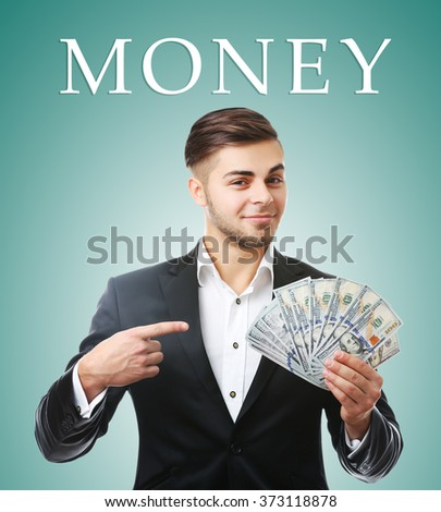 Man holding money on green background - stock photo