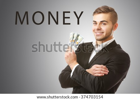 Man holding money on grey background - stock photo