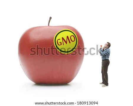 Man holding natural organic apple being bewildered when looking at giant GMO-modified red apple shot on white - stock photo