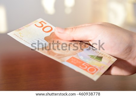 man holding new swedish 50 bank notes. NOTE: the new model.