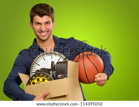 Man Holding Objects On Green Background