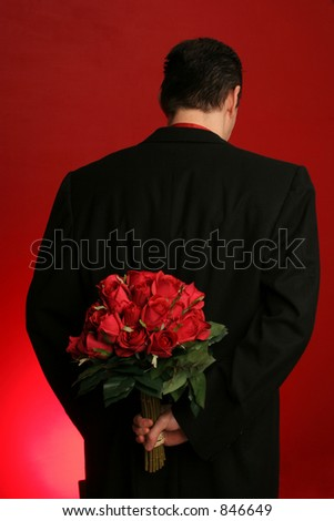 man holding out large bouquet of red roses behind his back on red backdrop - stock photo