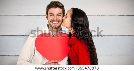 Man holding paper heart and being kissed by girlfriend against painted blue wooden planks - stock photo