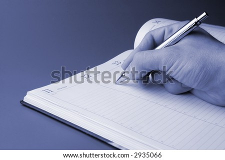 Man holding pen and writing in weekly planner - stock photo