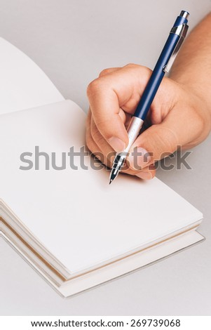 Man, holding pen in his hand and writing something in his note book. Place for text, closeup. - stock photo