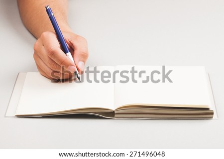Man, holding pen in his hand and writing something in note book. Place for text, closeup. - stock photo