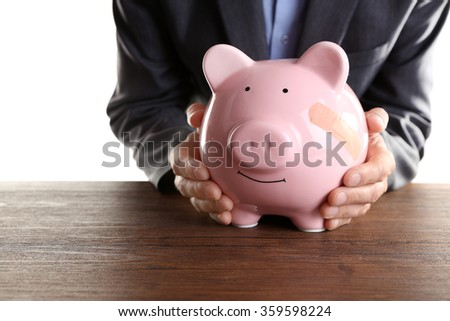 Man holding Piggy Bank with adhesive bandage, on white background