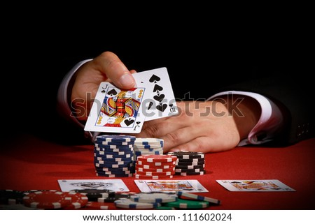 Man holding poker cards on red background - stock photo