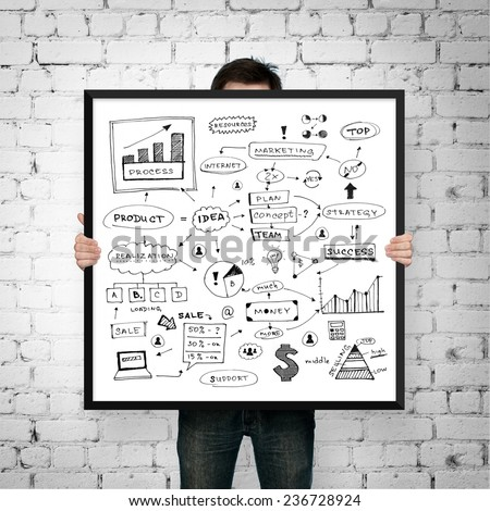 man holding poster business plan with frame on brick background - stock photo