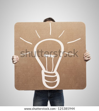 man holding poster with drawing lamp - stock photo