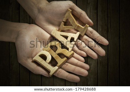 Man holding pray word in palm with wooden background - stock photo