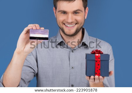 man holding present box with credit debit card. young happy excited guy holding credit card - stock photo