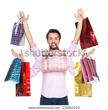 Man holding presents in gift paper bags, isolated on white. waist up of guy with four hands holding bag in his mouth - stock photo