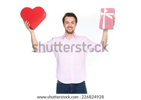 Man holding presents wrapped in gift paper, isolated on white. waist up of guy holding heart shaped boxes and smiling - stock photo