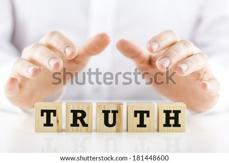 Man holding protective hands above the word Truth on a line of wooden cubes as he safeguards and protects them. - stock photo