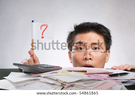 Man holding question mark flag made of paper and pencil with lots of bills in front of him - stock photo
