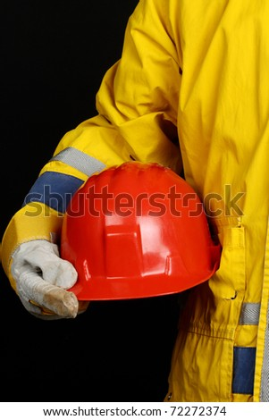 man holding red helmet over black background