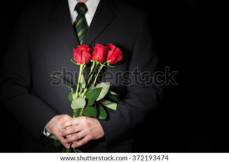 Man holding red roses. Valentine's day concept. Space for text. - stock photo