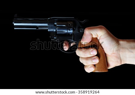 Man holding revolver on a dark background - stock photo