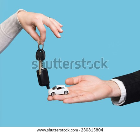 Man holding small car, woman holding car key on a blue background