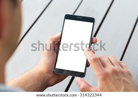 Man holding smart mobile phone on wooden table background - stock photo