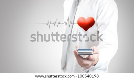 Man holding smart phone showing red heart and pulse - stock photo