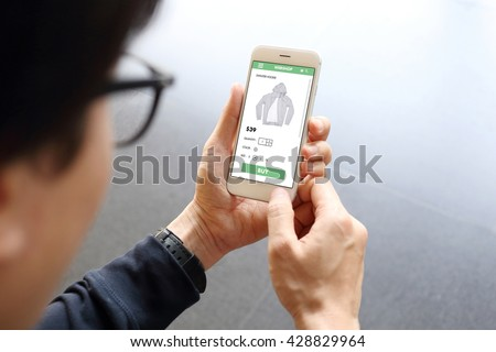 Man holding smartphone with buy sweater on ecommerce website - stock photo