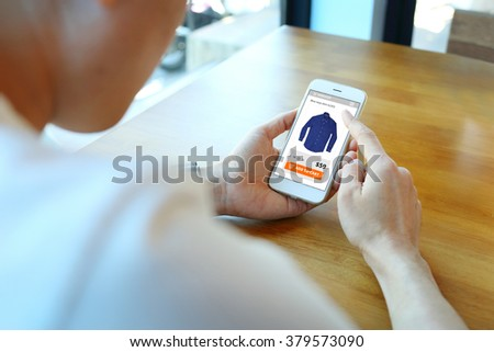 Man holding smartphone with choose shirt on ecommerce website - stock photo