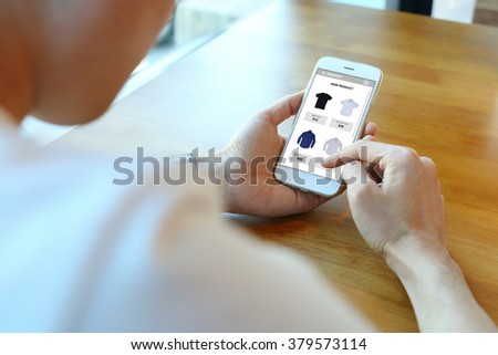 Man holding smartphone with choose shirt on ecommerce website